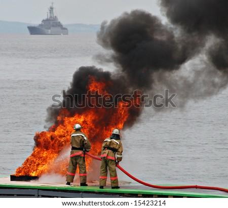 Firemen in fire, firefighting - stock photo