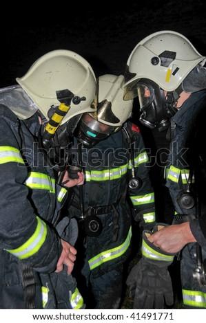 Firemen in respirators checking air tanks - stock photo