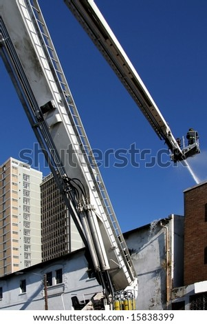 Firemen on an extended boom fighting a fire in a burning building with a water hose - stock photo