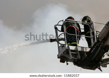 Firemen on an extended boom fighting a fire with a water hose - stock photo
