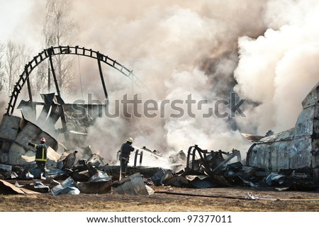 Firemen or firefighters putting out flames of crashed airplane or aircraft with clouds of white smoke. - stock photo