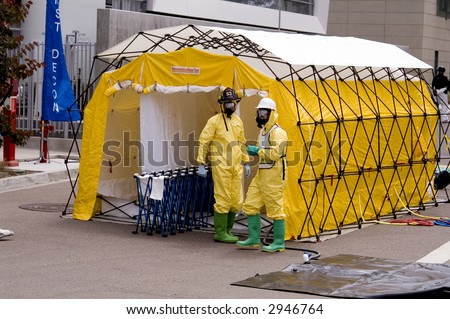 Firemen outside a decontamination shower - stock photo