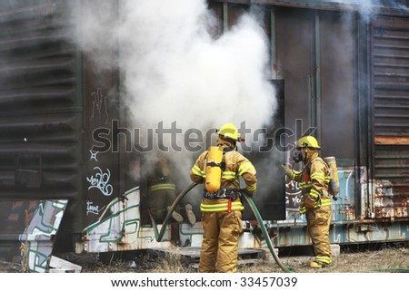 Firemen putting out a fire in a railway car - stock photo