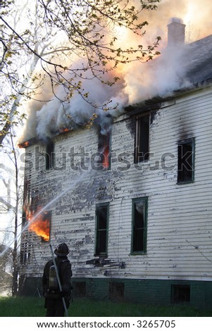 Firemen putting out a house fire in Detroit - stock photo