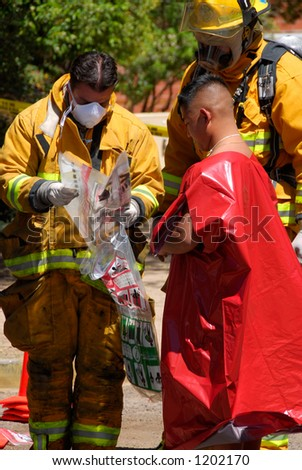 Firemen ready to decontaminate victim in terrorism drill - stock photo