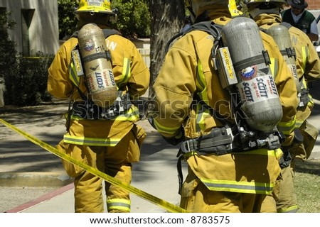 Firemen respond to an emergency wearing air packs - stock photo