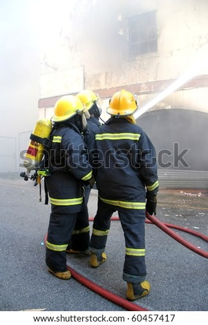 Firemen spraying water onto a burning building - stock photo