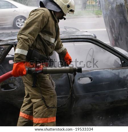 Firemen struggling against burning car - stock photo