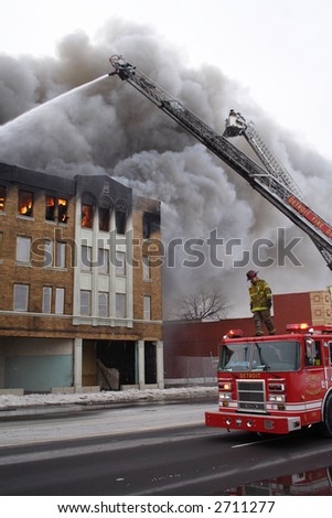 Firemen using their trucks to put out a huge fire - stock photo