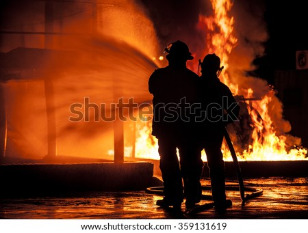 Firemen using water hose on fire