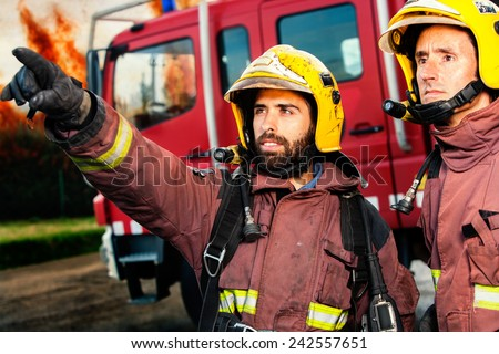 Firemen with fire truck and huge flames in background about to take action. - stock photo