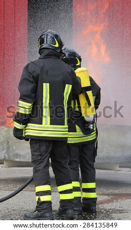 firemen with oxygen bottles off the fire during a training exercise