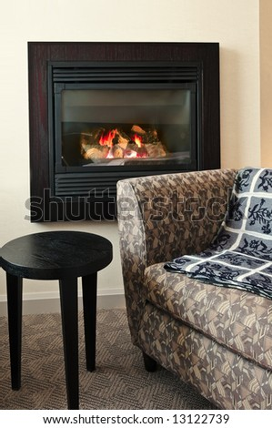 Fireplace and cozy armchair in living room - stock photo