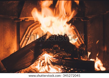 Fireplace burning. Warm cozy burning fire in a brick fireplace close up. Cozy background - stock photo