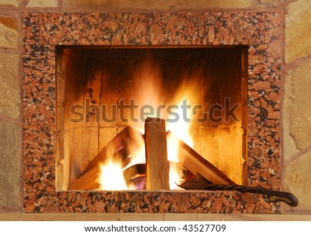 Fireplace. Flaring fire in a fireplace the reveted wild stone and a marble - stock photo