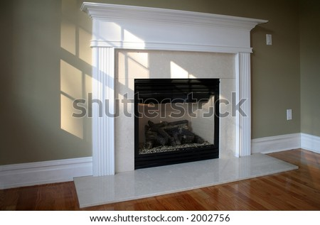 Fireplace in sunny room with white mantle; ambient window light - stock photo