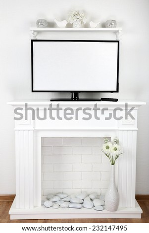 Fireplace with beautiful decorations and TV screen in comfortable living room - stock photo