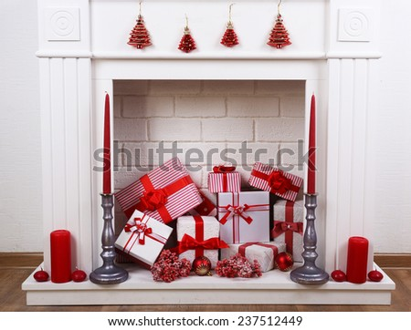 Fireplace with Christmas boxes and candles on wooden floor - stock photo