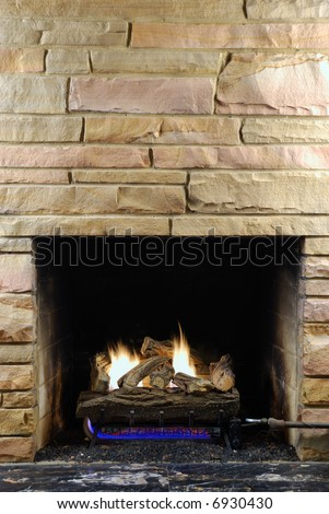 Fireplace with modern stone and gas logs - stock photo