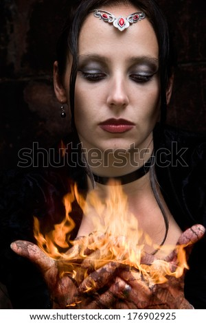 Firestarter - a woman with burning hands - stock photo