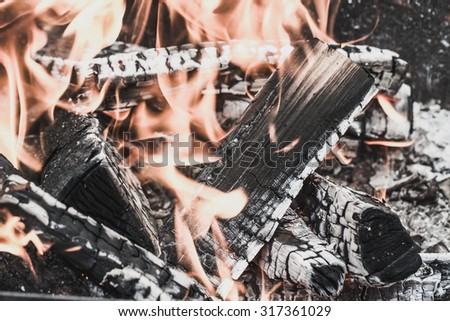 Firewood burning in fire. Selective focus. Toned. - stock photo