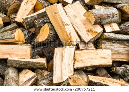 Firewood in a piece of wood stored on the stack - stock photo