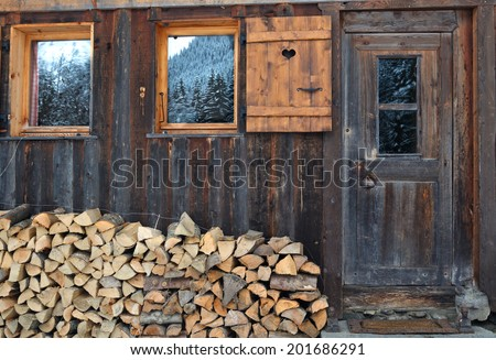 firewood stacked in front of a wooden chalet - stock photo
