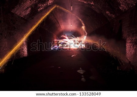firework explosion inside a dark tunnel at night - stock photo