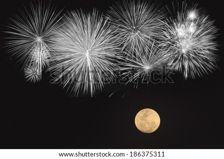 Fireworks and full moon  over black background - stock photo
