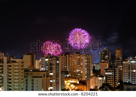 Fireworks behind the buildingsin the city .