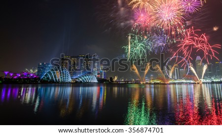 Fireworks displays along the Singapore River with Singapore Skylines, Downtown and Financial District buildings sparking reflection. Modern colorful City Background. Holiday urban night view. - stock photo