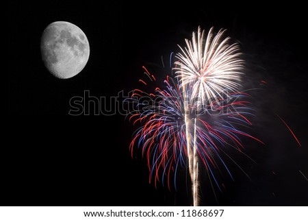 Fireworks exploding by the moon - stock photo