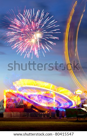 Fireworks exploding over rides at the fair - stock photo