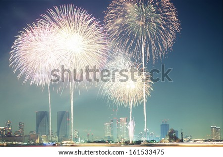 Fireworks filling the sky over tall skyscrapers. - stock photo