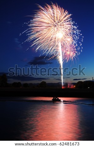 Fireworks firing up into the sky with a boat on a river below them, with a reflection - stock photo
