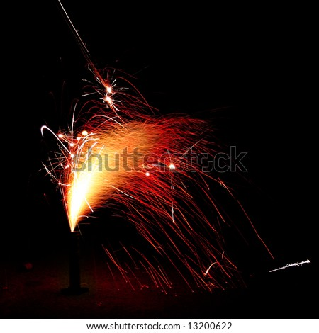 Fireworks giving off a shower of red & yellow sparks. - stock photo