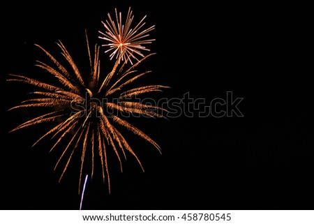 Fireworks in night sky with copy space on the right. - stock photo