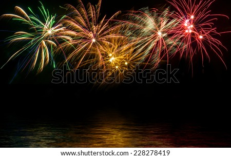 fireworks in the night sky reflected in water - stock photo