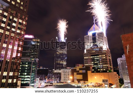 Fireworks launch from skyscrapers in downtown PIttsburgh, Pennsylvania, USA. - stock photo