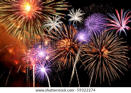 Fireworks of various colors bursting against a black background - stock photo