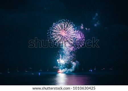 Fireworks on the water in Oahu, Hawaii. Boats can be seen on the sides of the fireworks. Colourful reflection on the water below.