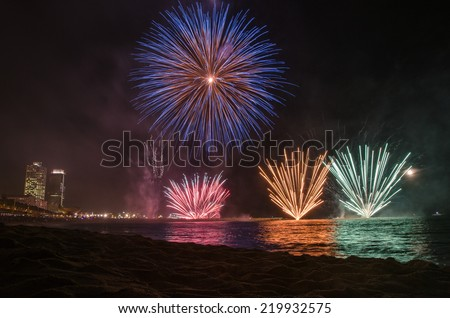 Fireworks on the water seen from the beach, in Barcelona - stock photo