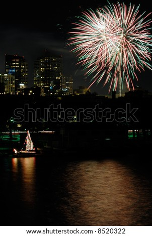 Fireworks over Boston. Colorful sailboat on Charles River. - stock photo