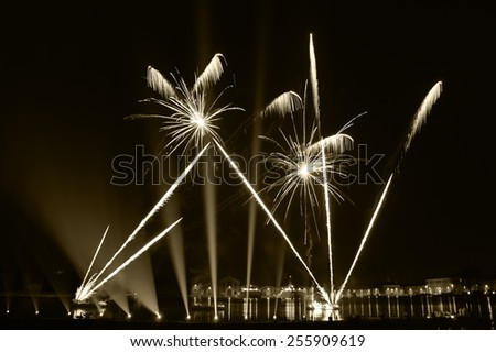 Fireworks over on the Arsenal lagoon during the Carnival celebration in Venice (Italy). Blurred lights. Aged photo. Sepia. - stock photo