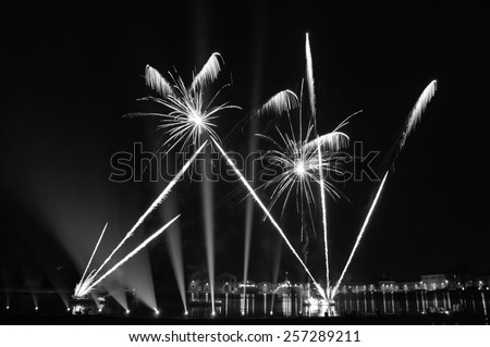 Fireworks over on the Arsenal lagoon during the Carnival celebration in Venice (Italy). Blurred lights. Aged photo. Black and white. - stock photo