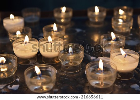 firing candles in catholic church on dark background