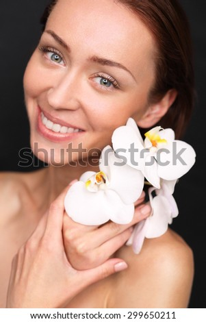 Firm and elastic skin, the natural beauty of women. Portrait of beautiful young happy woman with white orchid flowers