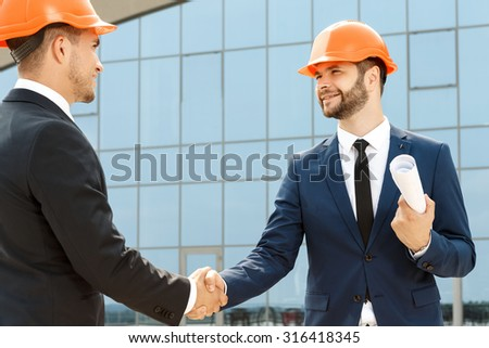 Firm handshake of two handsome colleagues outdoors - stock photo