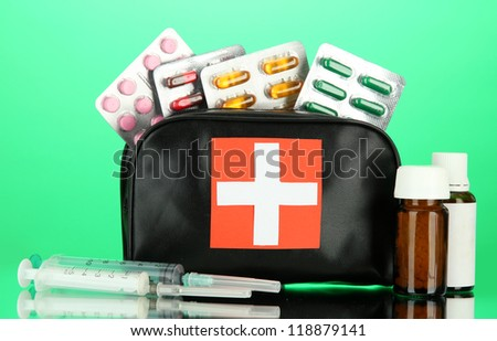 First aid bag, on green background - stock photo