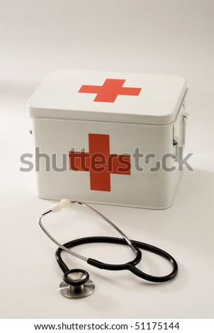 First aid box in white background and a stethoscope in foreground.